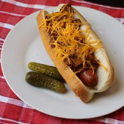chili dog on plate with pickles