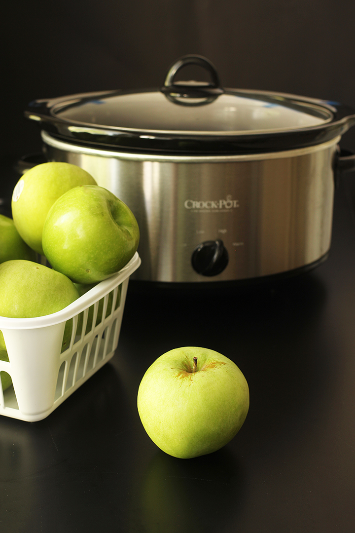 green apples in basket next to black slowcooker