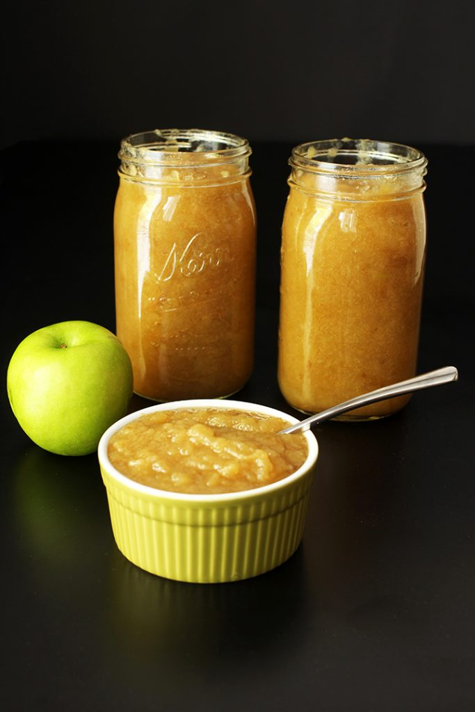 jars of applesauce with green apple and green bowl of sauce