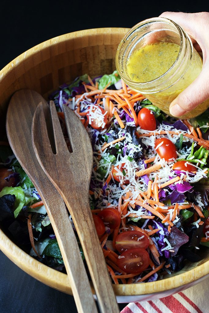 pouring herbed vinaigrette into salad bowl