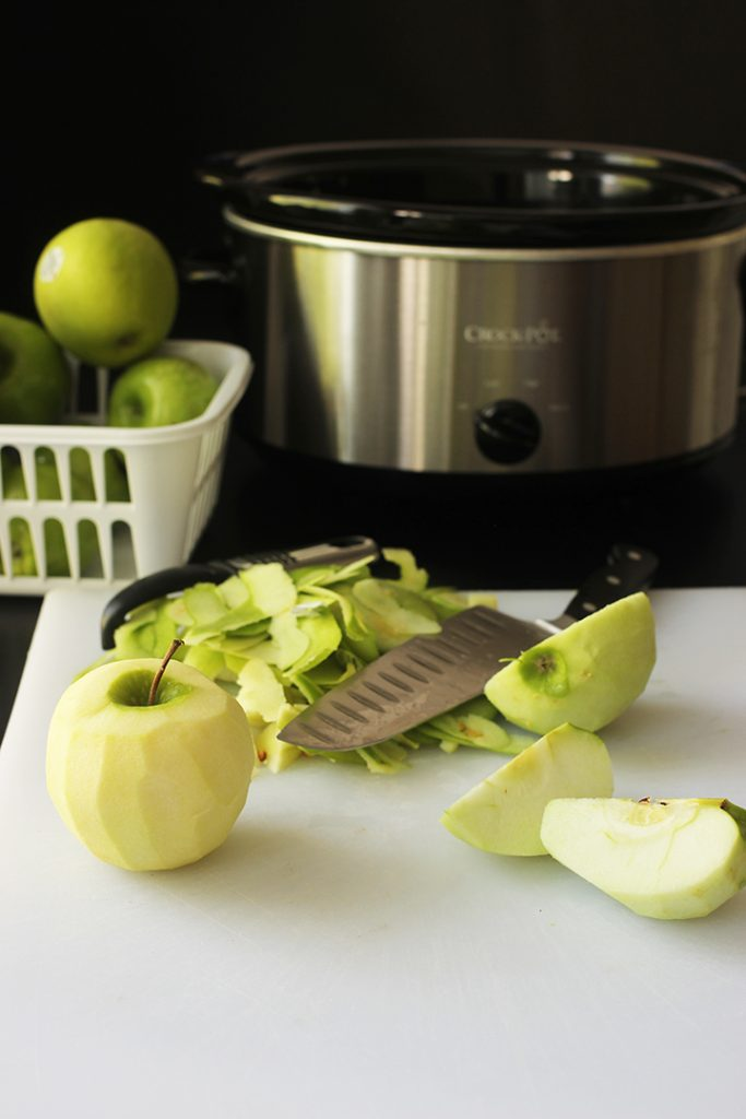 slowcooker next to basket of apples and cutting board with knife, peelings, and cut apples