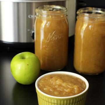 A bowl of applesauce on a table, next to jars and apple