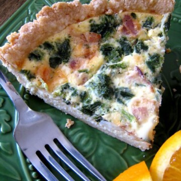 A piece of Quiche on a plate with a fork