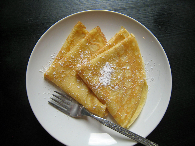 A plate of folded crepes with powdered sugar