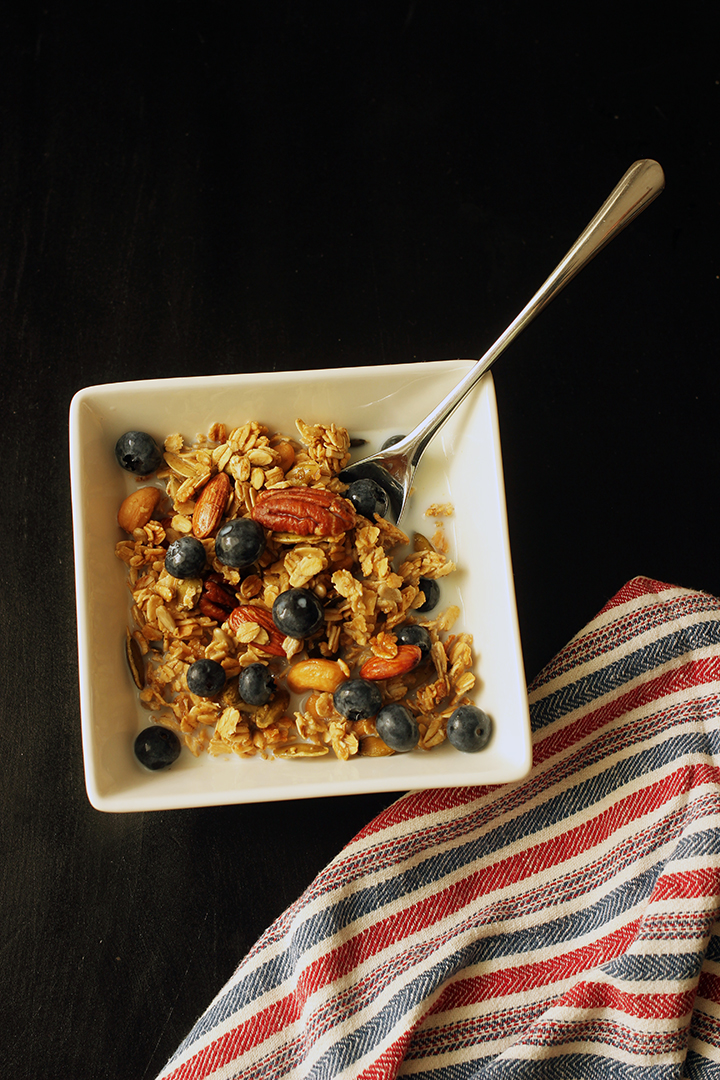maple granola in square bowl with berries and milk