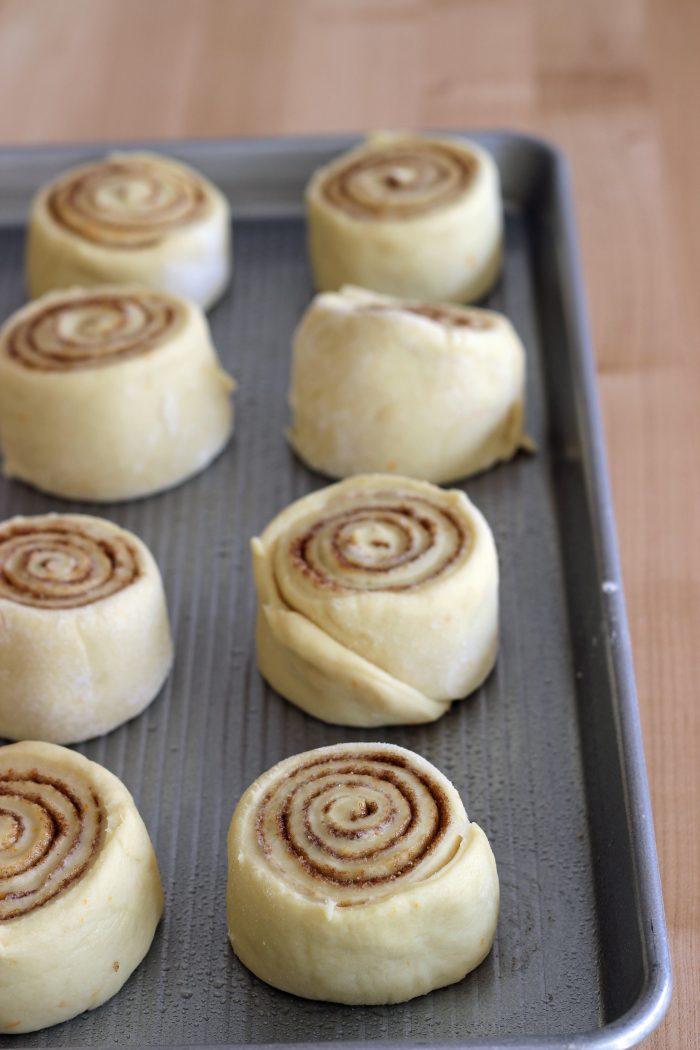 unbaked cinnamon rolls on open tray on counter