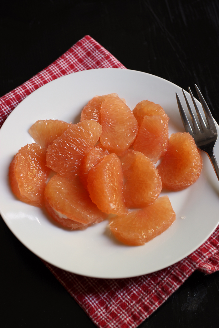 Grapefruit sections on a plate with a fork