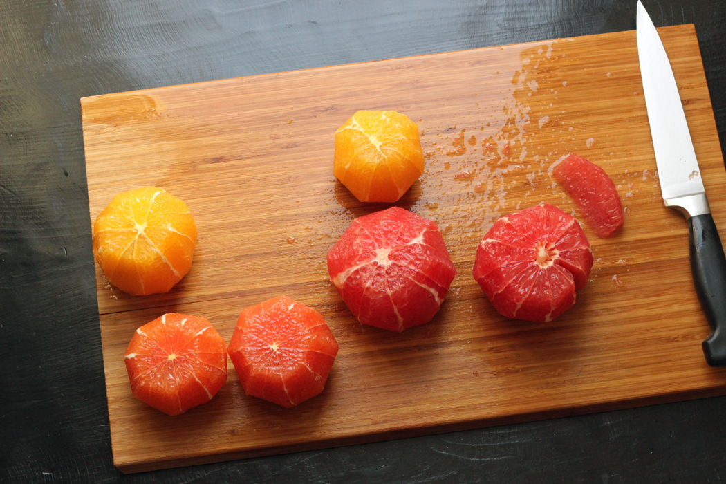 a variety of oranges and grapefruits on a cutting board with a knife