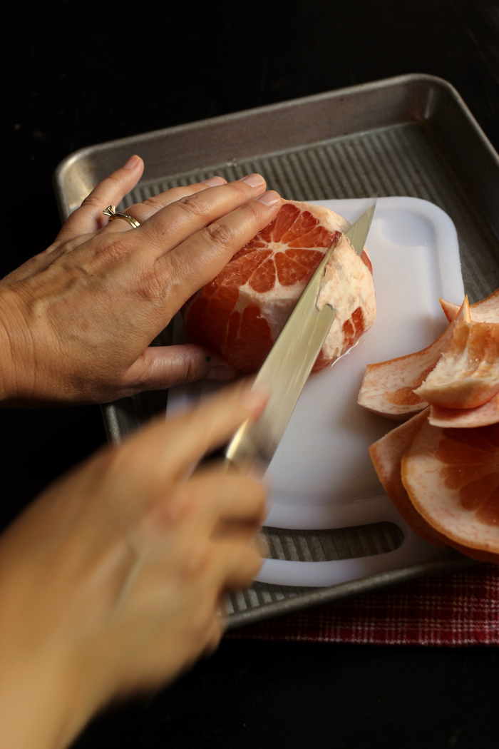 Knife cutting away the white pith layer from the grapefruit
