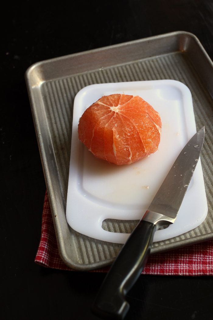 grapefruit with the rind and pith cut away, knife, and cutting board