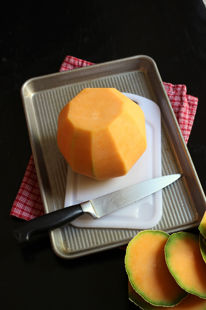 melon on cutting board placed in rimmed baking sheet