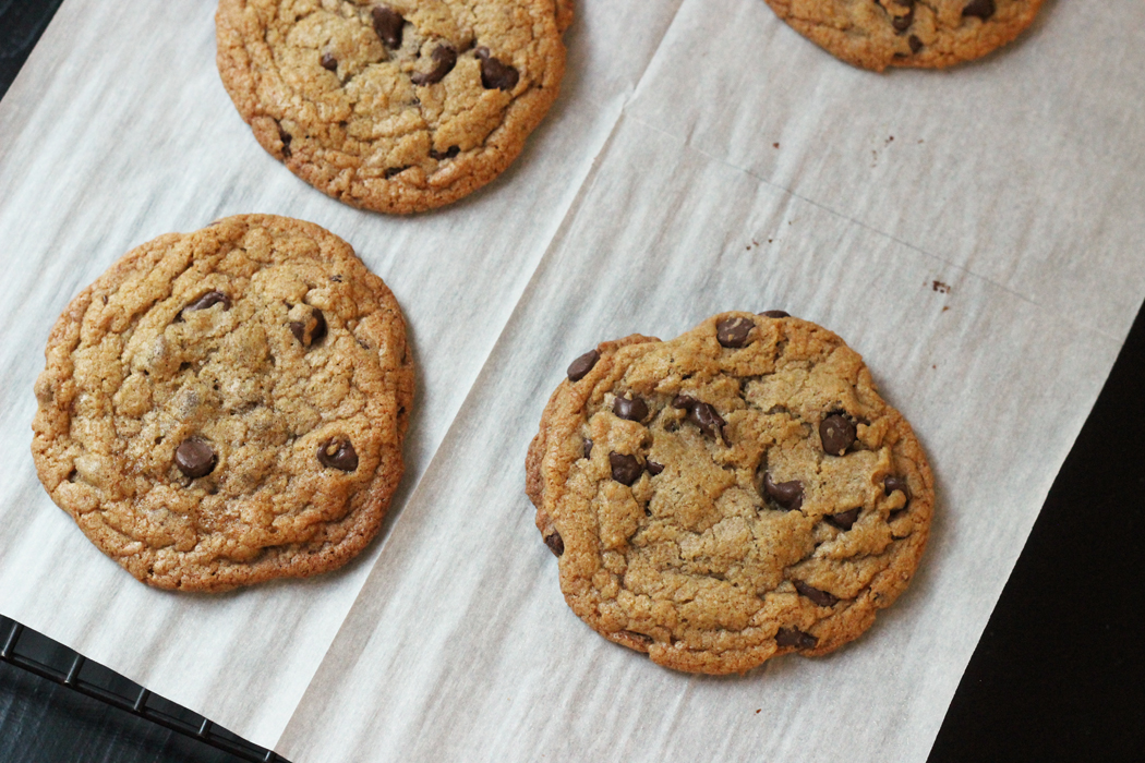 Thick and Chewy Chocolate Chip Cookies on parchment paper