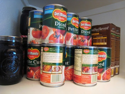 cans of tomatoes stacked in pantry