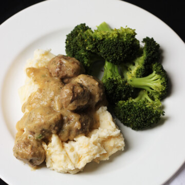 A plate of meatballs, mashed potatoes, and broccoli