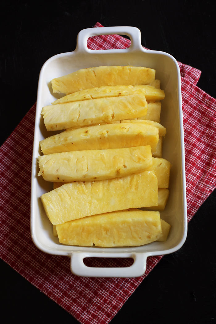 pineapple spears in dish with red cloth underneath
