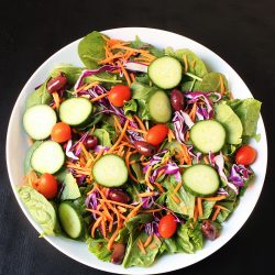 salad piled with cucumbers tomatoes olives and carrots