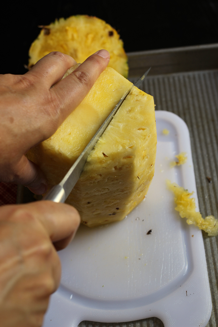 woman's hands cutting around the pineapple core