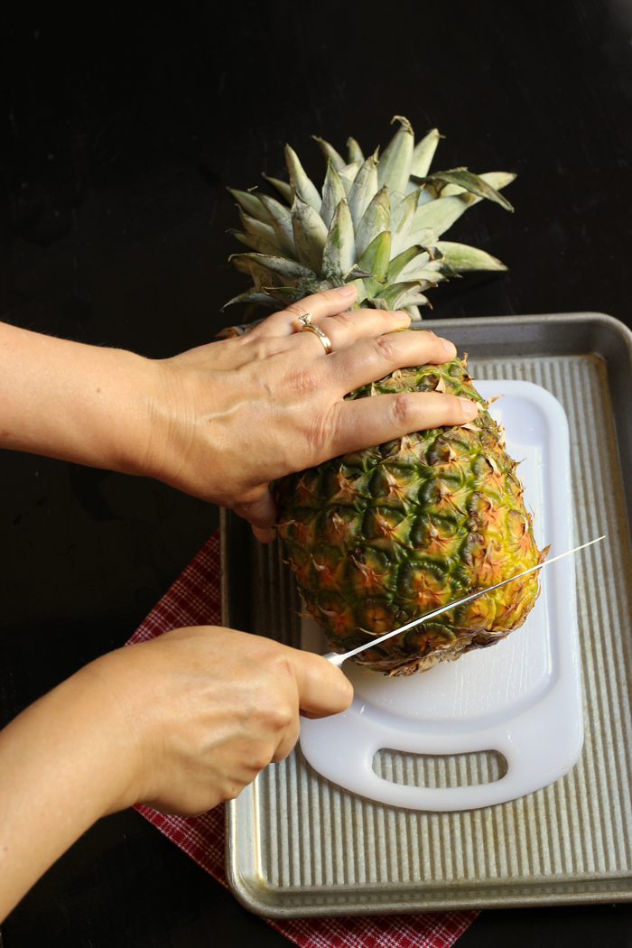 woman's hands cutting off bottom of pineapple