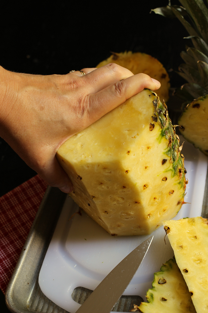 woman's hands trimming skin of pineapple