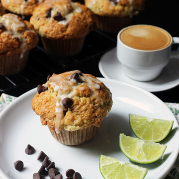 chocolate chip muffin on plate on table next to cooling rack with espresso