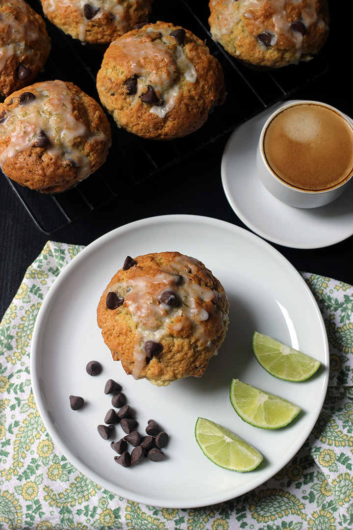rack of muffins next to a plate with a muffin, chocolate chips, and lime wedges