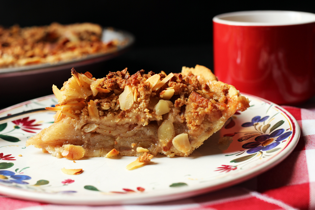 slice of apple pie on a plate with coffee cup on the side