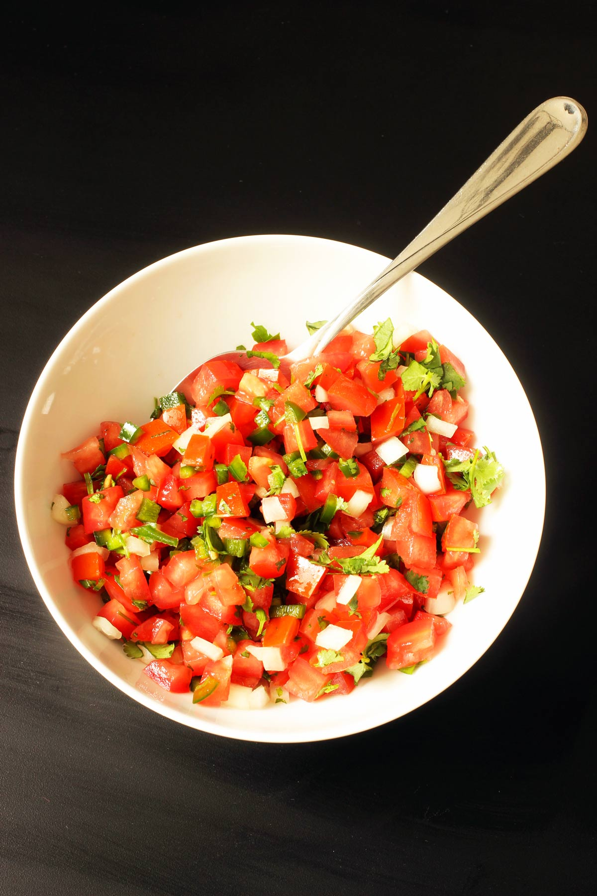 finished bowl of pico de gallo in white bowl with large spoon.
