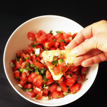 dipping chip in white bowl of pico de gallo.