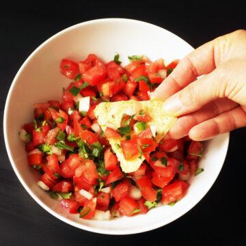 hand dipping chip into bowl of pico de gallo.