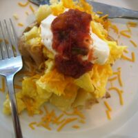 loaded breakfast potato on a plate with fork