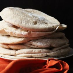 stack of pita breads near orange napkin