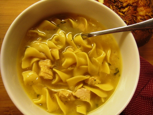 A bowl of turkey noodle soup and a spoon