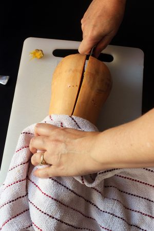 A close up of a hand slicing squash in half