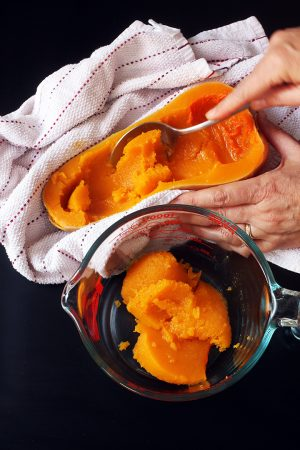 hand scooping out flesh of cooked Squash