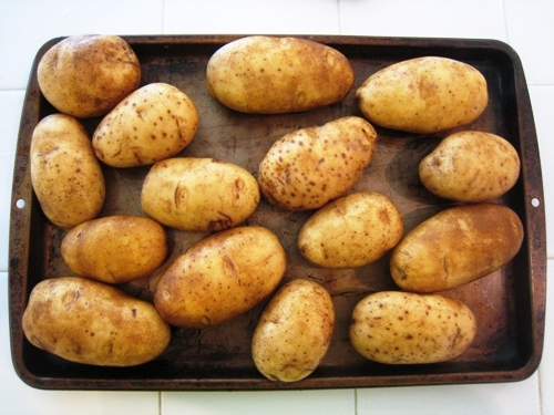 cookie sheet with baking potatoes on it