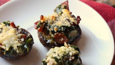 three stuffed mushrooms on plate with platter of mushrooms in background
