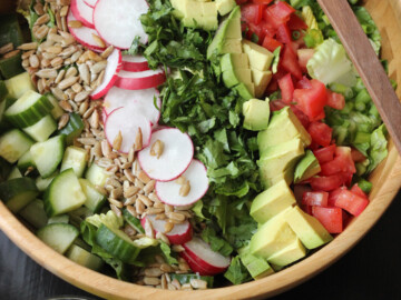 A bowl of chopped salad with radish and avocado