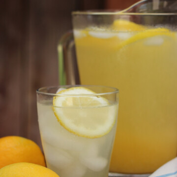 A pitcher of Lemonade on a table with lemons