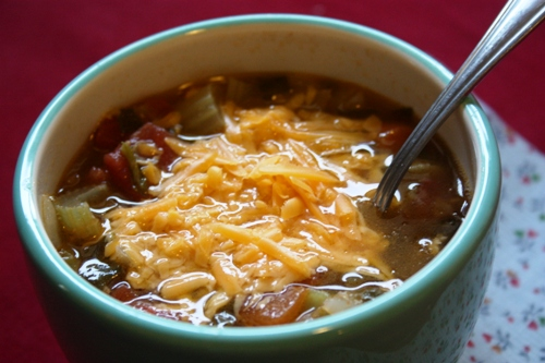 lentil soup in a bowl topped with cheddar