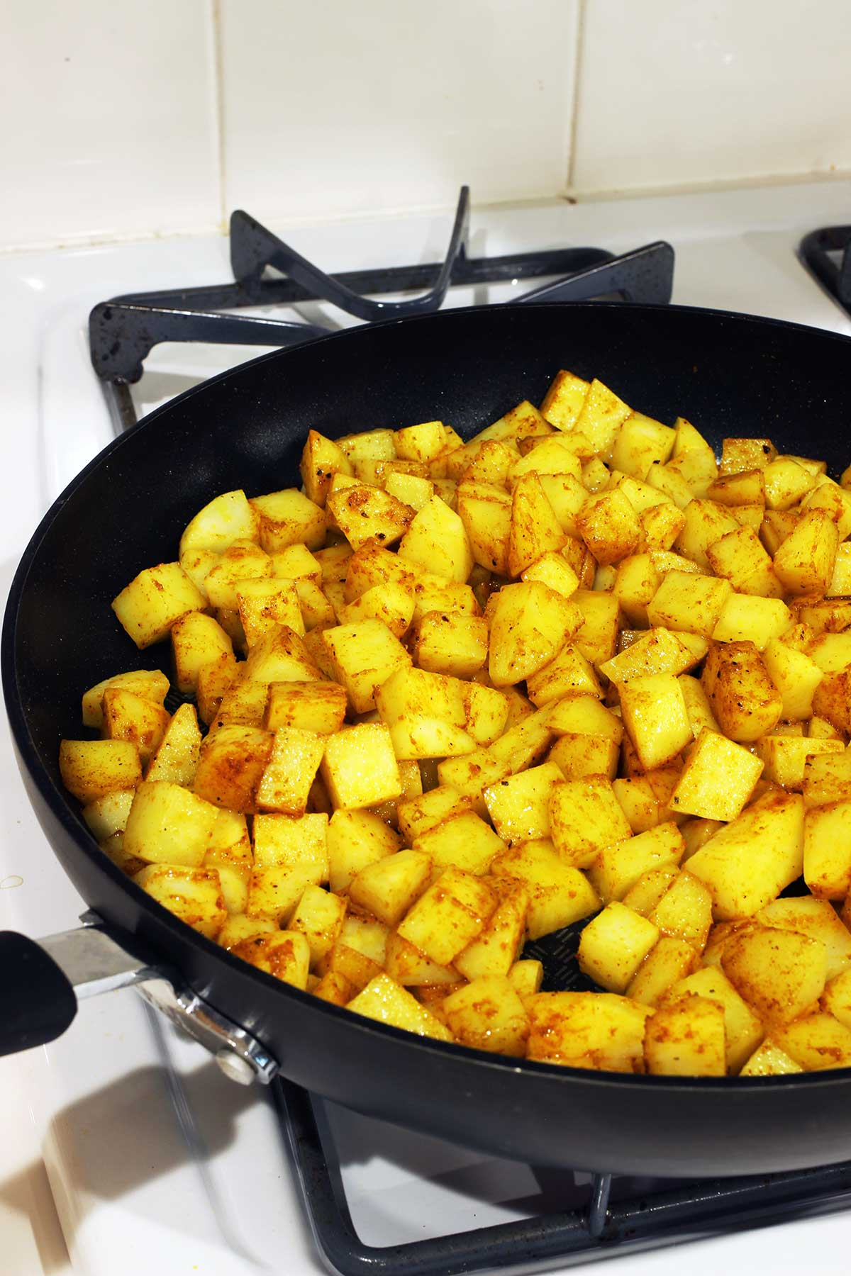 cooking curried potatoes in skillet