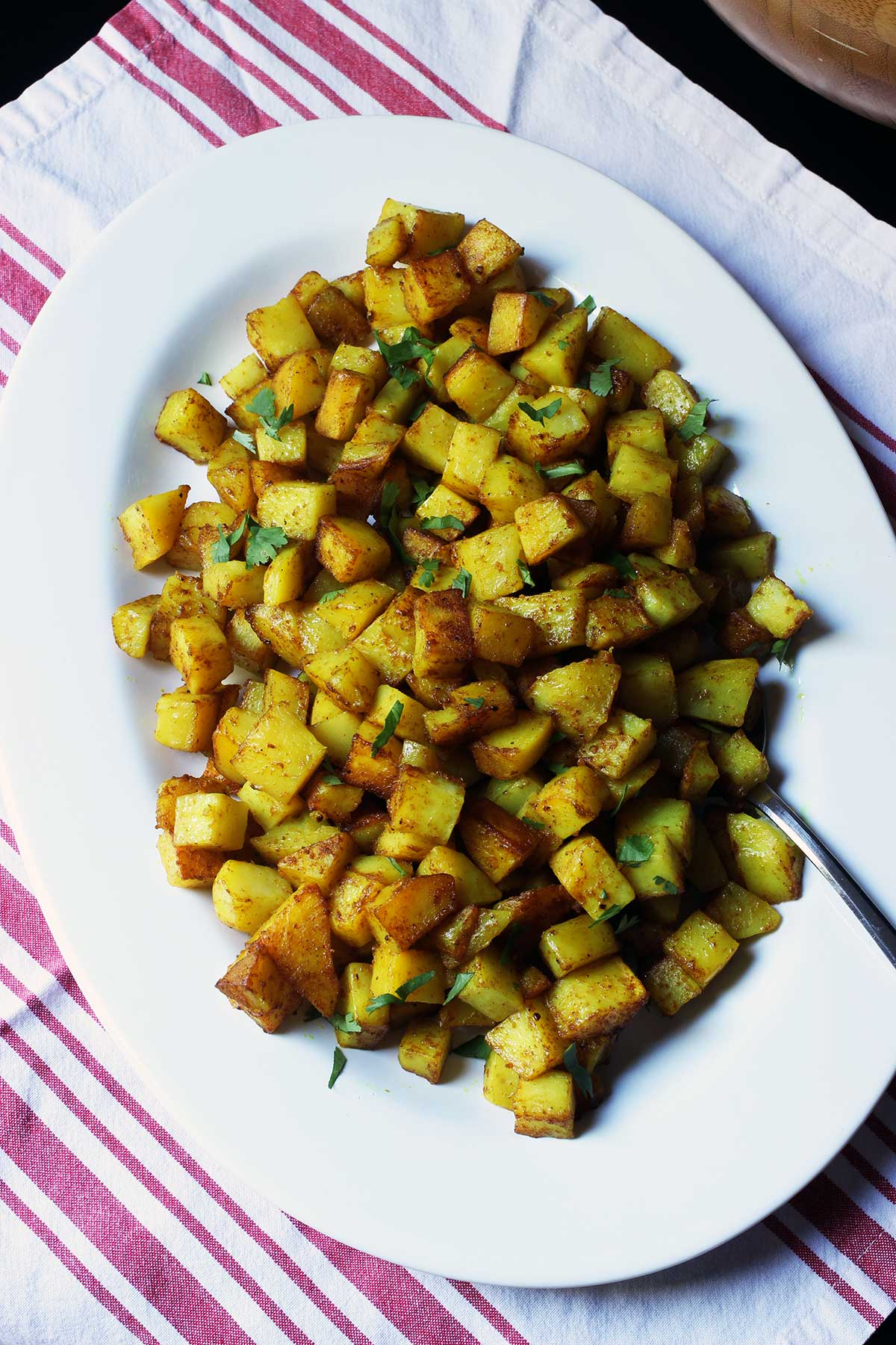 large oval platter of curried potatoes