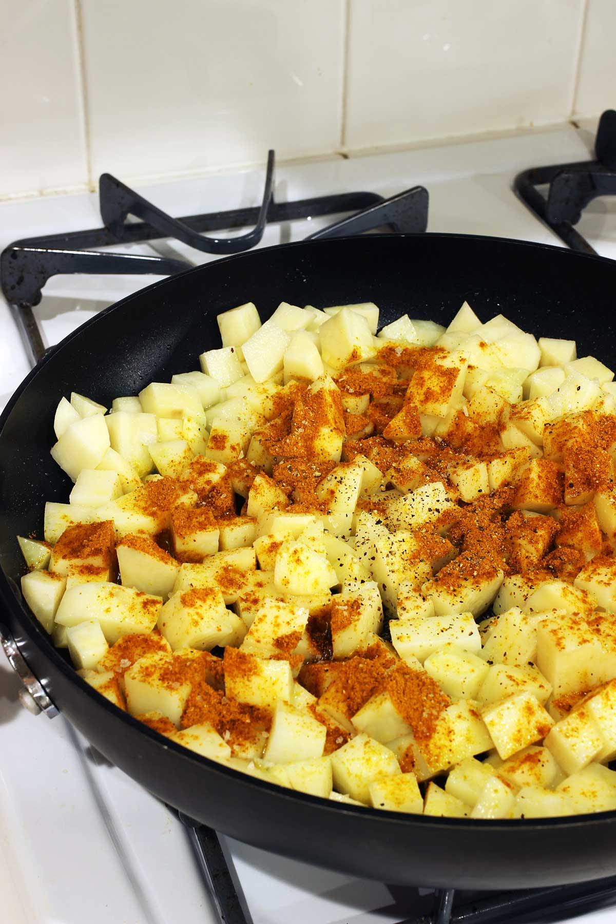 potatoes in skillet with seasonings
