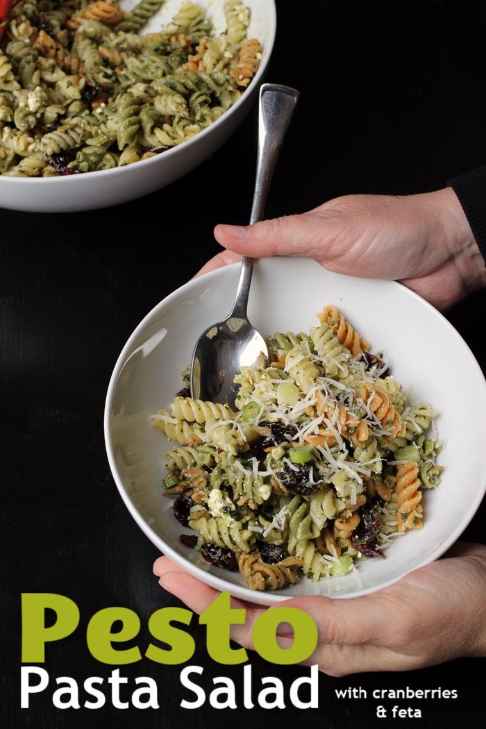 A person holding a bowl of Pesto Pasta Salad