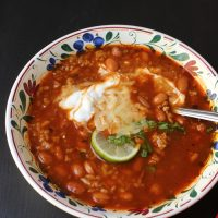 bowl of bean soup with sour cream cheese and lime