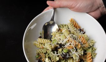hands holiding bowl of Pesto Cranberry Pasta Salad