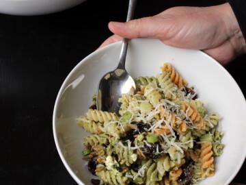 hands holiding bowl of Pesto Cranberry Pasta Salad