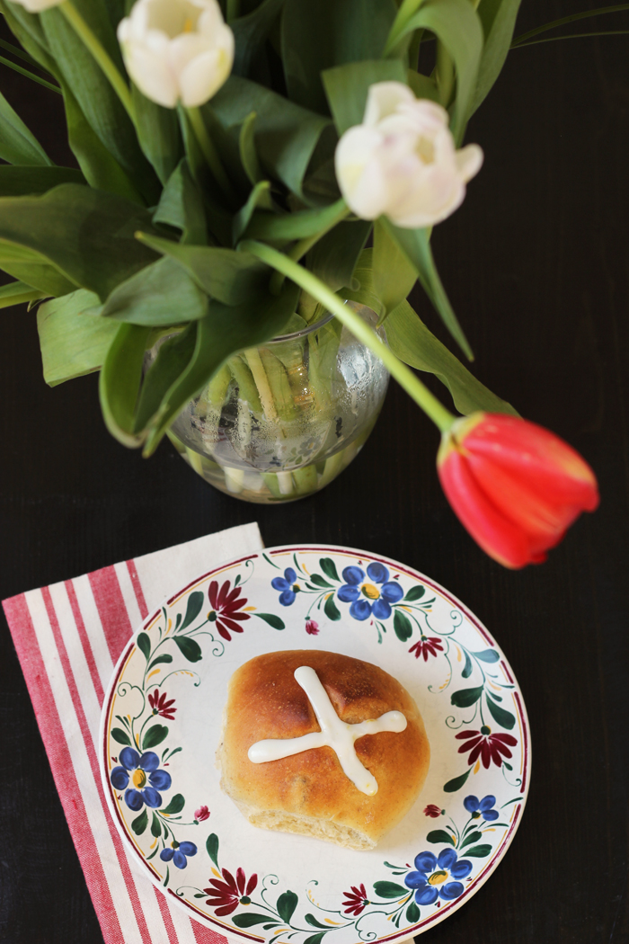 hot cross bun on a plate next to vase of flowers