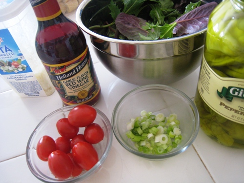 A bottle of vinegar and a bowl of Salad
