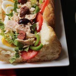 A close up of a Pan Bagnat sandwich on a plate