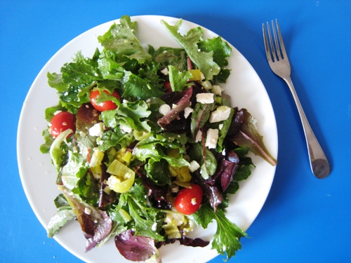 A bowl of salad on a blue table